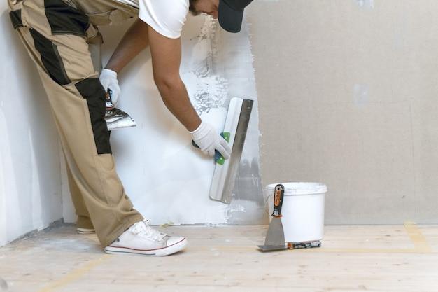 Männlicher maler mit einem spatel in den händen repariert zu hause. raumrenovierungskonzept.