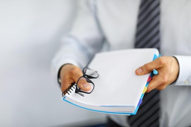 Männlicher manager brachte ein notizbuch für notizen und einen stift. mitarbeiter mit krawatte hält ein notizbuch an einer feder und eine brille