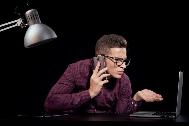 Männlicher manager drinnen mit brille, die am telefon spricht