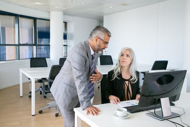Männlicher manager erklärt seinen bericht der chefin. kollegen sitzen und stehen am arbeitsplatz mit pc und diskutieren diagramm. geschäftskommunikationskonzept