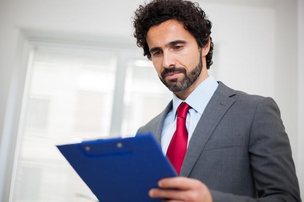 Männlicher manager in den bürolesedokumenten
