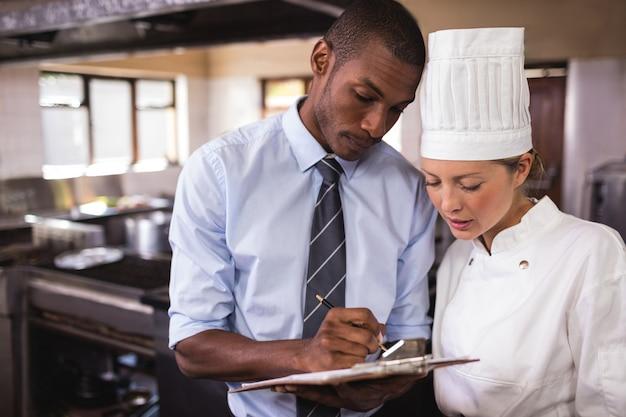 Männlicher manager und weibliches chefschreiben auf klemmbrett in der küche