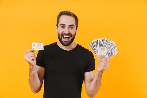 Männlicher mann, der ein einfaches schwarzes t-shirt trägt, das geld bargeld und kreditkarte isoliert über gelber wand hält