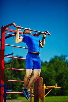 Männlicher mann hübschen gesunden glücklichen srtong athleten, der am stadtpark - eignungskonzepte an einem schönen sommertag auf horizontaler stange trainiert