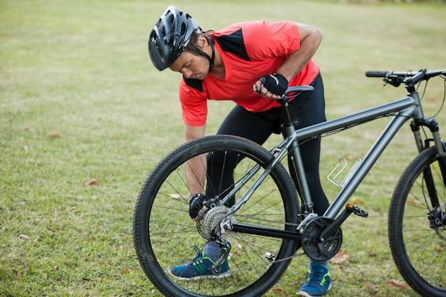 Männlicher mann mountainbiker, der seine fahrradkette repariert