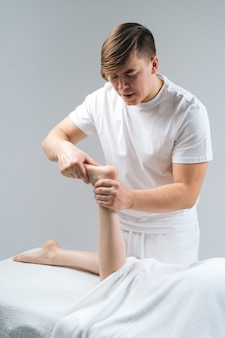 Männlicher masseur, der der jungen frau, die auf massagetisch auf weißem hintergrund liegt, füße massiert. professioneller physiotherapeut mit starken händen, der fußmassage durchführt. konzept der massage-spa-behandlungen