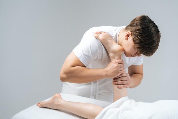 Männlicher masseur mit starken händen massiert den unteren teil des beins an die junge frau, die auf dem massagetisch liegt