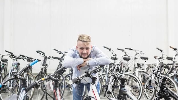 Männlicher mechaniker, der auf fahrrad in der werkstatt sich lehnt