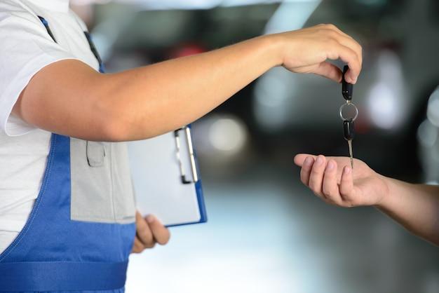 Männlicher mechaniker, der dem kunden autoschlüssel gibt.