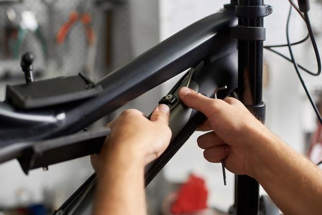 Männlicher mechaniker, der dienst in der fahrradreparaturwerkstatt unter verwendung der werkzeuge herstellt