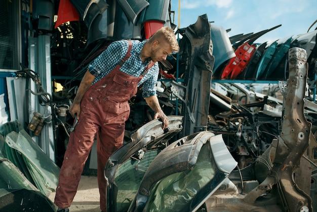 Männlicher mechaniker, der ersatzteile auf autoschrottplatz wählt