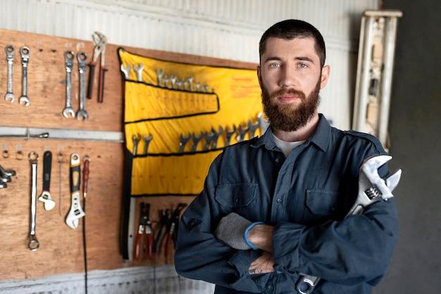 Männlicher mechaniker, der in seiner werkstatt arbeitet