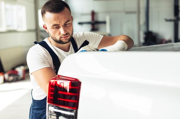 Männlicher mechaniker der seitenansicht, der rückseite des autos überprüft