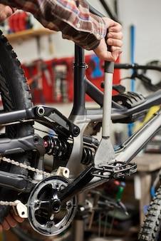 Männlicher mechaniker, der service in fahrradreparaturwerkstatt mit werkzeugen herstellt