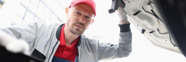 Männlicher mechaniker, der unter der motorhaube des autos schaut