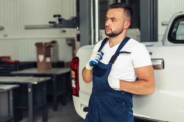 Männlicher mechaniker der vorderansicht, der auf auto sich lehnt
