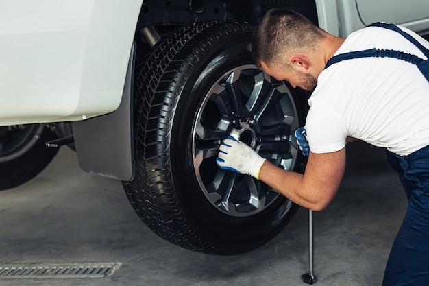 Männlicher mechaniker des hohen winkels, der rad ersetzt