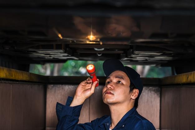 Männlicher mechaniker hält und leuchtende taschenlampe zur überprüfung unter autoproblem
