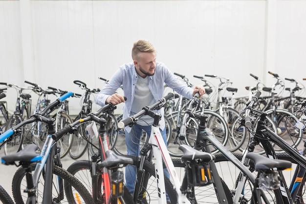 Männlicher mechaniker mit verschiedenen arten von fahrrädern im shop
