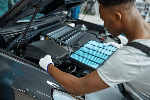 Männlicher mechaniker wechselt luftfilter, autoservice. fahrzeugreparaturwerkstatt, mann in uniform, innenraum der autostation