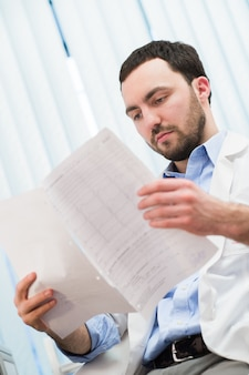 Männlicher medizinarzt, der etwas an seinen papieren überprüft. medizinische versorgung, versicherung, verschreibung, papierkram oder karrierekonzept. arzt bereit, patienten zu untersuchen und zu helfen.