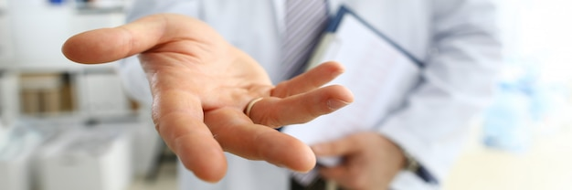 Männlicher medizinarzt, der helfende handnahaufnahme anbietet