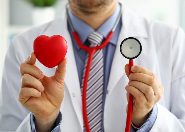 Männlicher medizinarzt, der rotes herz und stethoskop hält