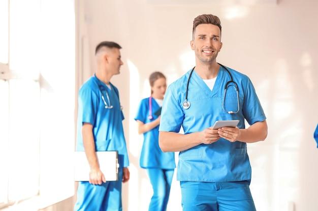 Männlicher medizinstudent mit tablet-computer in der halle der klinik