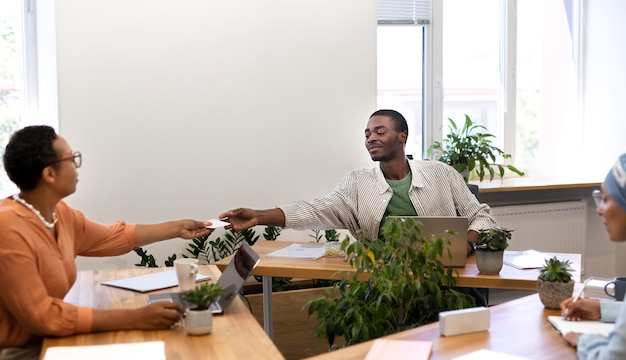 Männlicher mitarbeiter im gespräch mit seinen neuen kollegen im bürojob