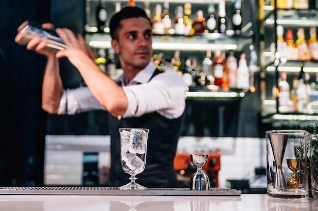 Männlicher mixologe macht rotes cocktail durch rütteln.