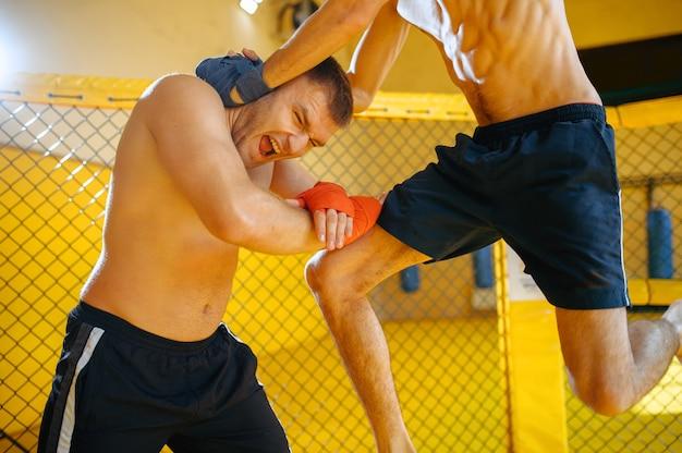 Männlicher mma-kämpfer blockiert knietreffer in einem käfig im fitnessstudio.