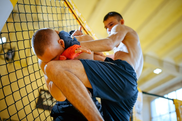 Männlicher mma-kämpfer führt seinem gegner in einem käfig im fitnessstudio einen knietreffer zu.