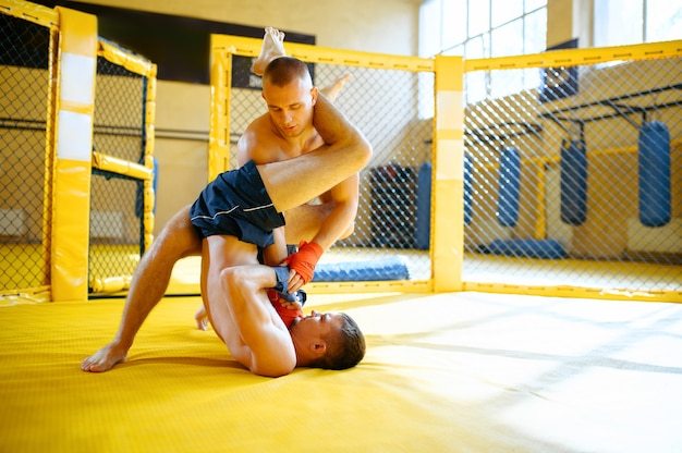 Männlicher mma-kämpfer hält seinen gegner in einem käfig im fitnessstudio schmerzhaft fest.