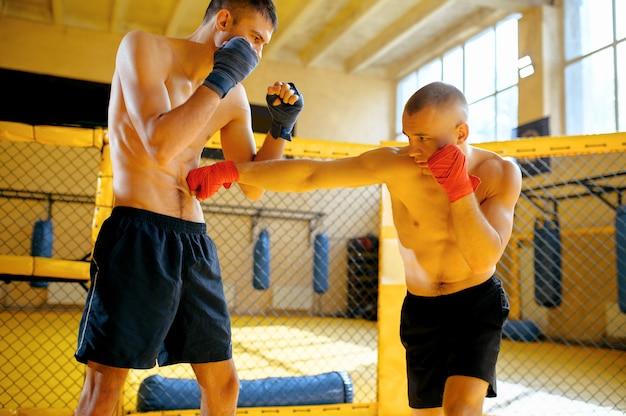 Männlicher mma-kämpfer schlägt seinen gegner in einem käfig im fitnessstudio.