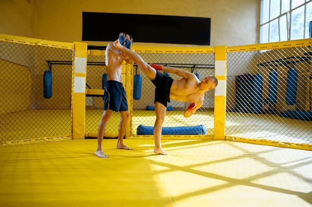 Männlicher mma-kämpfer tritt seinem gegner in einem käfig im fitnessstudio einen hohen tritt zu.