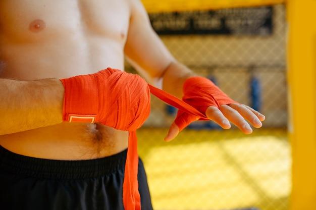 Männlicher mma-kämpfer wickelt bandagen an seinen händen im fitnessstudio.