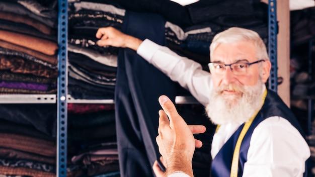 Männlicher modedesigner, der gewebe vom regal für seinen kunden nimmt