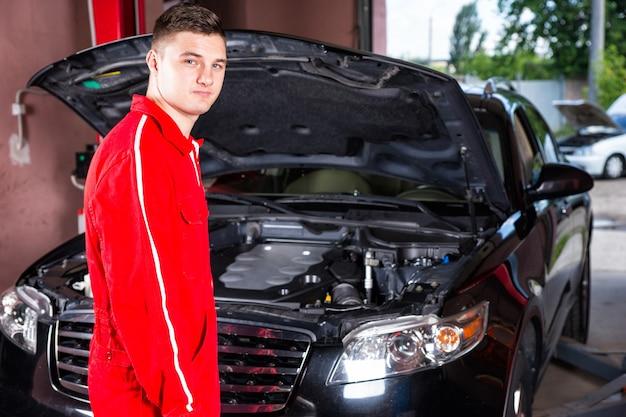 Männlicher motormechaniker in uniform, der nahe einer schwarzen limousine steht