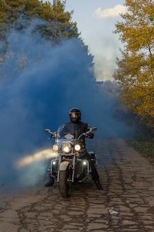 Männlicher motorradfahrer im sturzhelm auf fahrrad im schönen herbstvordergrund