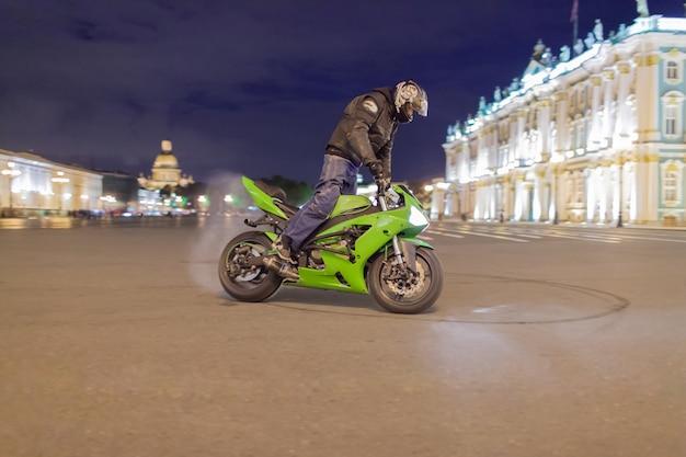 Männlicher motorradfahrer trieb nacht auf ihrem sportmotorrad.