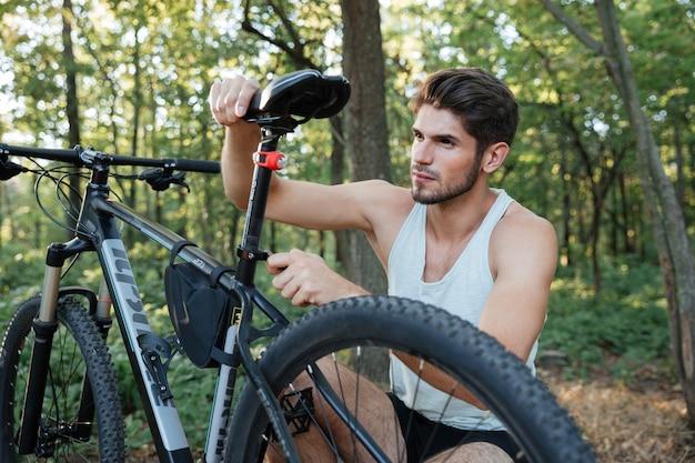 Männlicher mountainbiker, der sein fahrrad im wald repariert