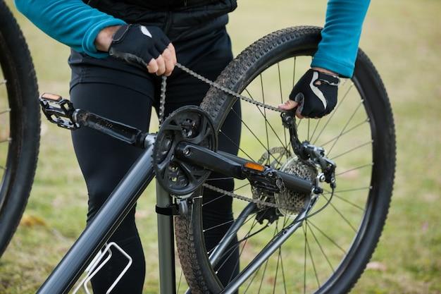 Männlicher mountainbiker, der seine fahrradkette repariert