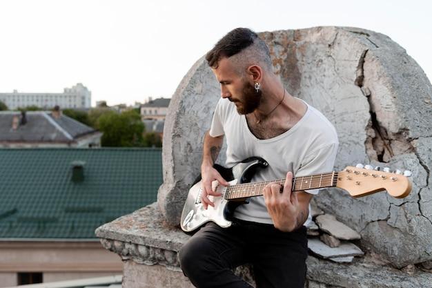 Männlicher musiker auf dach, der e-gitarre spielt