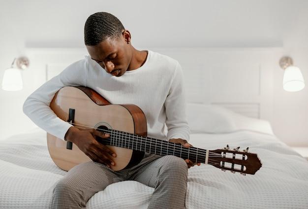 Männlicher musiker auf dem bett, das gitarre spielt