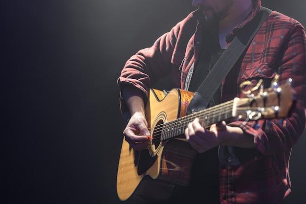 Männlicher musiker, der akustische gitarre in einem dunklen raumkopierraum spielt.