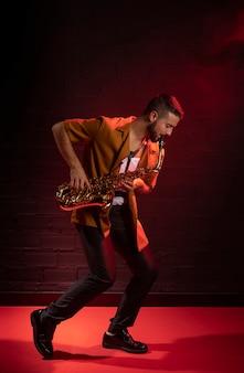 Männlicher musiker, der das saxophon im nebel mit kopierraum spielt