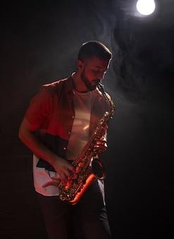 Männlicher musiker, der das saxophon im rampenlicht spielt