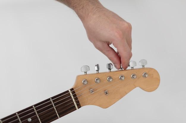 Männlicher musiker, der eine e-gitarre abstimmt