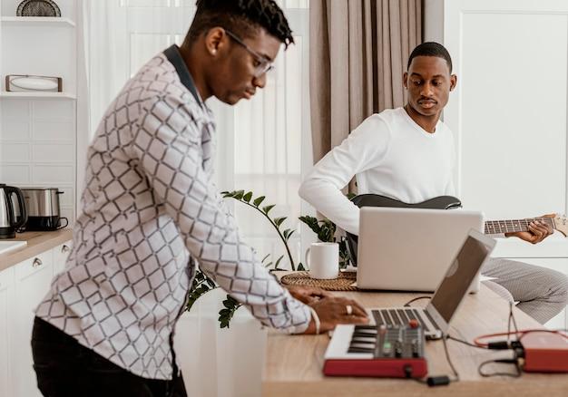 Männlicher musiker, der elektrische gitarre und mannaufzeichnung mit laptop spielt