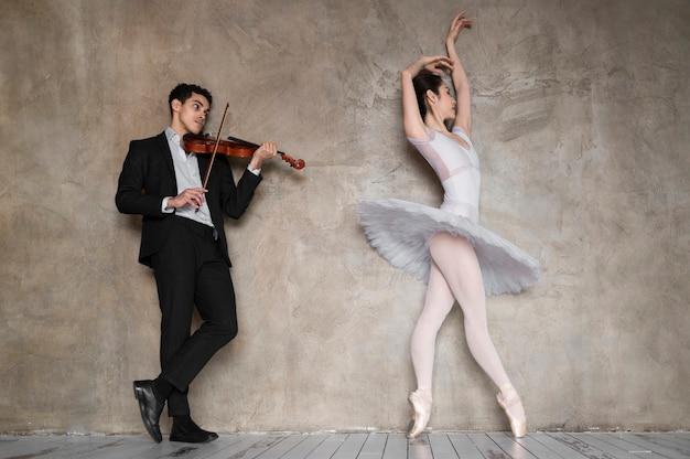 Männlicher musiker, der geige spielt, während ballerina tanzt